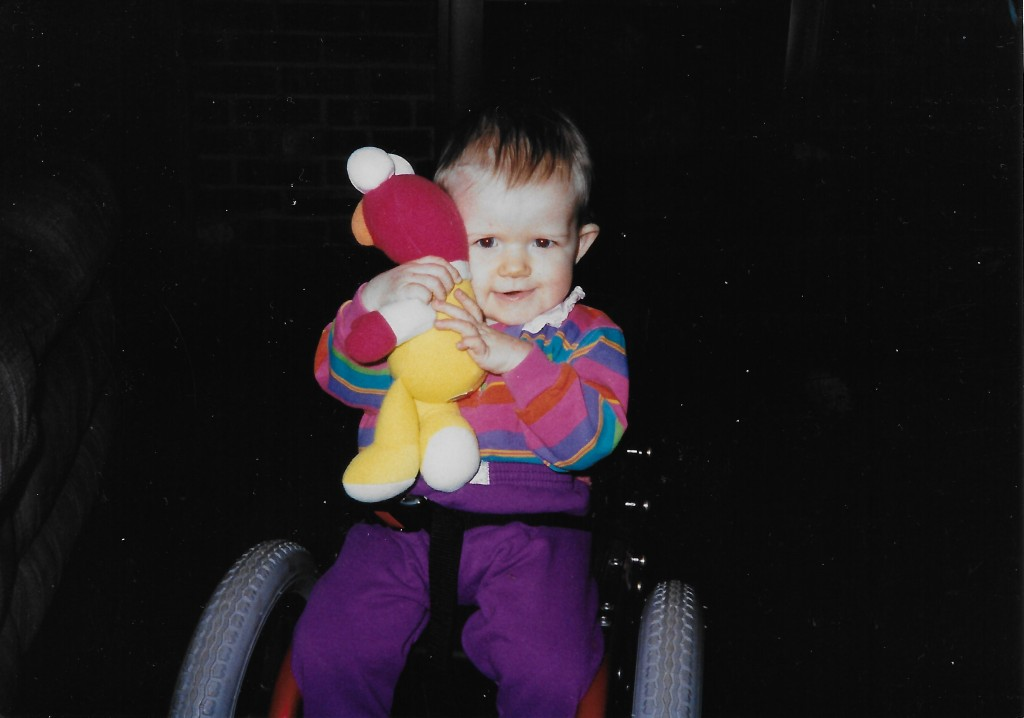 Hugging my doll; Sitting in my first wheelchair