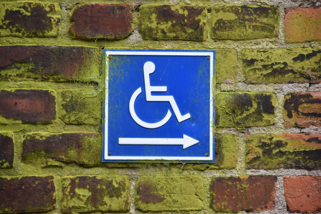 Blue wheelchair entrance sign with arrow on red brick wall